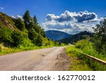 Empty asphalt mountain road with near the coniferous forest with cloudy sky in morning light - stock photo