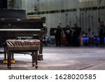 Small photo of St. Joseph, MO / United States of America - Oct 14th 2019: A Steinway and Sons grand piano and bench sit on stage, while a cast and crew prepare for a dress rehearsal in the background of the theater.