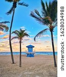 Small photo of Typical american blue lifeguard house on Florida beach in Hollywood USA. Beautiful tropical Floridian landscape with tall palm trees, ocean and lifeguard house at sunset. Popular american landmark.