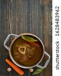 Small photo of Paleo bone broth diet, beef meat soup. Low-carb food, keto recipe. Rich broth of slow languishing on beef and bones, prolonged boiling. Long cooking in pan. Dark wooden table, vertical, copy space