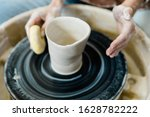 Small photo of And unbalanced and lopsided imperfect clay pot being made on a pottery wheel by a student who is learning how to throw pots on a pottery wheel