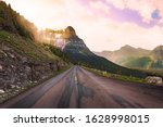 On the Going to the Sun Road in Montana, with bright sunlight streaming through the trees - stock photo