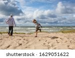 Small photo of Brothers playing on the beach on a blustery spring day, focus on small boys face, some motion blur