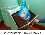 Throwing out garbage Packed in a garbage bag using a home trash chute in Russia. refuse chute