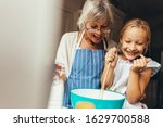 Small photo of Happy grandmother and kid mixing a cake batter at home. Happy little girl stirring batter in a bowl with her granny standing by her side.