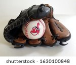 Small photo of Chicago, IL September 9, 2019, Close up view of a white baseball ball Chief Wahoo Cleveland Indians mascot logo inside tan baseball glove on a white neutral background, major league baseball, Louisvi