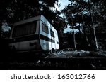Vintage camper van on a parking lot at the night - horror movie scene - stock photo