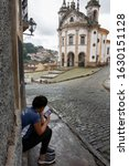 Small photo of OURO PRETO, MINAS GERAIS, BRAZIL - DECEMBER 22, 2019: An unidentified woman uses her phone in Largo do Rosario, Ouro Preto - Brazil. Ouro Preto was designed a World Heritage Site by UNESCO in 1980