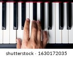 Small photo of right hand playing a D Major chord on the piano