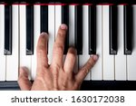 Small photo of right hand playing a C Minor chord on the piano