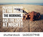 Christian inspirational quote - Prayer should be the key in the morning, and the lock at night. With wooden rosary with Jesus Christ holy cross crucifix on natural wood table and blue sea background.