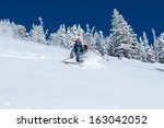 Woman Skiing Deep Powder Near...