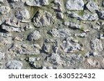 The stony wall texture background made of big wild rocky stones bonded by the cement in one construction