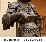 Small photo of Sculpture of King Arthur old metal statue. Medieval knights armor full size standing warrior. Order of the Knights Templar and an iron knight's armour