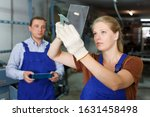 Small photo of Confident young woman in blue overalls working in glass workshop, measuring glass with trammel before cutting