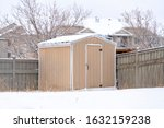 Wooden Shed With Snowy Roof At...