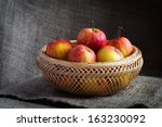 Apples in wooden basket on sack cloths - stock photo