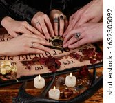 Small photo of People conducting a seance using a Ouija Board, or Talking Spirit Board, with white candles. Shot from overhead. Occultism.