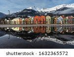 Water reflection of the distinctive colored house fronts of the Mariahilf district and Nordkette of Innsbruck, Austria captured from Marktplatz