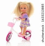 Small photo of Small plastic baby girl toy on bicycle. Isolated on white background with shadow reflection. Girl toy on bike with auxiliary wheels and wire basket. Caucasian missy plaything with long blonde hair.