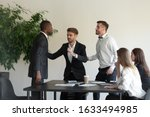 Small photo of During group meeting African and Caucasian business partners having conflict fighting, colleague stop a scuffle, multiracial people express aggression negative attitude, racial discrimination concept