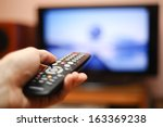 watching tv and using remote... | Shutterstock . vector #163369238