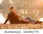 young couple sitting near lake... | Shutterstock . vector #163381775