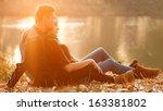 Young Couple Sitting Near Lake  ...