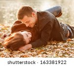 young couple lying down near... | Shutterstock . vector #163381922