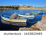 The old Fatimid port of Mahdia, Tunisia, with colorful fishing boats and the mosque lighthouse in the background