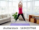 Small photo of Young fitness woman doing jumping jacks or star jump exercise at home, copy space. Girl working out, full length portrait. Healthy lifestyle concept