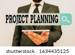 Small photo of Conceptual hand writing showing Project Planning. Business photo showcasing plan and subsequently report progress within the project Male human wear formal work suit hold smartphone using hand.