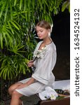 Small photo of Luxurious blonde woman with white flowers in her hand sitting on massage table. Exotic tropical style exterior. Spa and welness