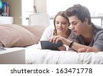 beautiful teenage couple using...   Shutterstock . vector #163471778