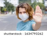 Girl, young woman in protective sterile medical mask on her face looking at camera outdoors, on asian street show palm, hand, stop no sign. Air pollution, virus, Chinese pandemic coronavirus concept.
