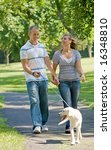 Stock photo young couple walking dog 16348810