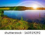 Morning mountain lake and forest on the embankment - stock photo