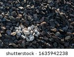 Small photo of Heart is laid out of white rounded stones against dark brown and gray granite of railway embankment. Concept of Valentine's day: Gentle, light feeling against the background of rough, uncouth reality