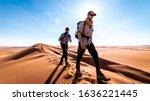 Two Men Trekking The Wahiba...