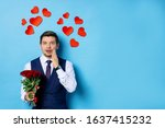 portrait of shocked caucasian man with roses isolated over blue background, male in tux, in formal suit. small red hearts over his head. man dumbfounded by love