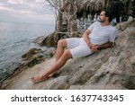 A Man Sits On A Stone By The...