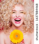 Small photo of Beautiful fashionable blonde girl in retro style with voluminous curly hairstyle, bare shoulders and a sunflower in her hands on a red background. Happy girl laughing