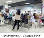 Small photo of Patients on wheelchairs waiting for seeing doctor at the outpatient department , nurse takes care some patient in Thailand hospital, blurred background.
