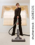 Young woman in a business suit vacuuming in an exaggerated pose. Selective focus on vacuum. - stock photo