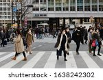 Small photo of TOKYO, JAPAN - February 7, 2020: Shibuya's large scramble crossing. People are wearing face masks during the coronavirus outbreak. Some motion blur.