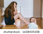 Small photo of The concept of maternal burnout, postpartum depression, regret and unjustified expectations. Tired young mother sits in the bedroom on the floor, a half-year-old baby crawls nearby.