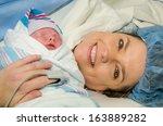 mother hugs her new infant... | Shutterstock . vector #163889282