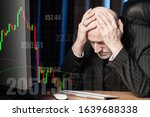 Small photo of A man clutched his head against the backdrop of falling stock prices. Receiving losses on the exchange. Fluctuations in exchange rates. Profit or loss. Risk of exchange operations. Exchange hedge.