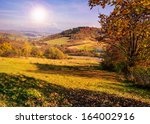 autumn landscape. forest on a hillside covered with red and yellow leaves. over the mountains against blue sky clouds - stock photo