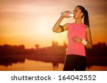 thirsty female runner  outdoor | Shutterstock . vector #164042552